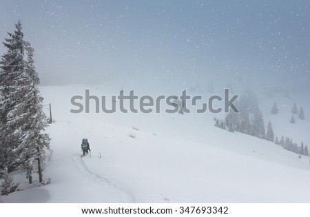 Tourists with backpacks climb to the top of the mountain in fog and snow fall.