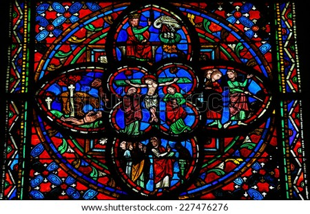 TOURS, FRANCE - AUGUST 8, 2014: Stained glass window dating from the 13th Century in the Cathedral of Tours, France. This window depicts the Crucifixion of Jesus in the center. - stock photo