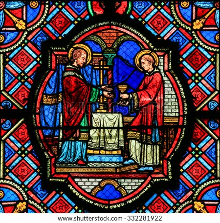 TOURS, FRANCE - AUGUST 14, 2014: Stained glass window depicting Jesus and a Saint with the Eucharist in the Cathedral of Tours, France. - stock photo