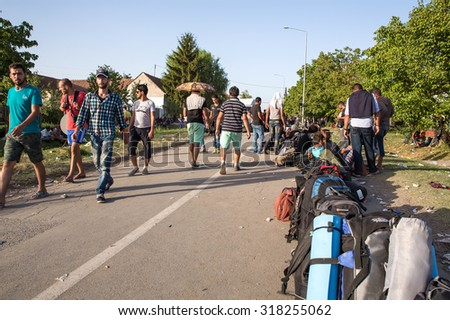 TOVARNIK, CROATIA - SEPTEMBER 18: Stranded Refugees form a waiting line in order to get a transported further towards northern Europe on September 18, 2015 in Tovarnik, Croatia. 
