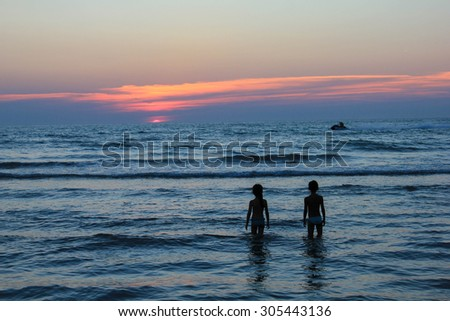 Tow children's silhouettes in the sea at sunset