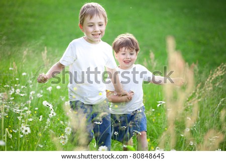 Tow cute preschool siblings holding hands and running through field of long grass. - stock photo