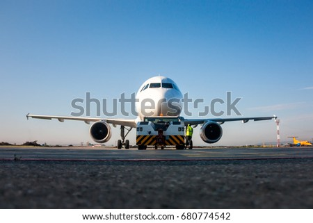 Tow truck is pushing back the passenger airplane