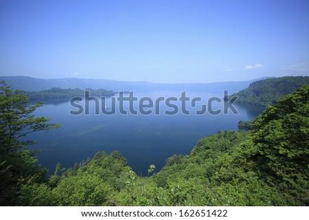 Towadako and a pleasure boat - stock photo
