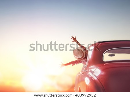 Toward adventure! Girl relaxing and enjoying road trip. Happy girl rides into the sunset in vintage car. - stock photo