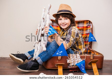 Towards the adventures! Little boy in headwear holding wheel and looking at camera while sitting in suitcase and holding a big steering wheel  - stock photo