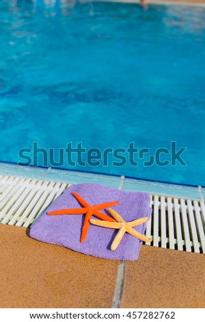 Towel and star fishes at the swimming pool - stock photo