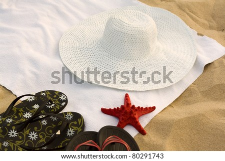 Towel, flip-flops, a hat and a starfish on the beach - stock photo