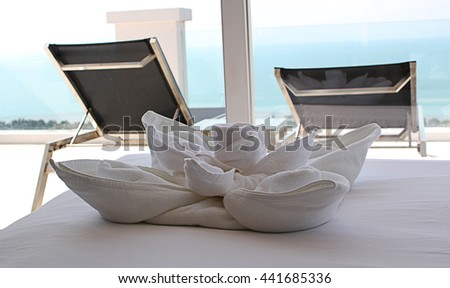 Towel on bed in hotel room and  beach view - stock photo