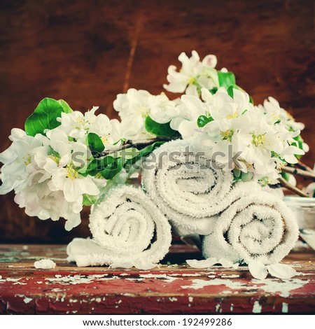 Towels and Blossoming Branch of an Apple-tree in Aroma SPA Set on Wooden Background, vintage style - stock photo