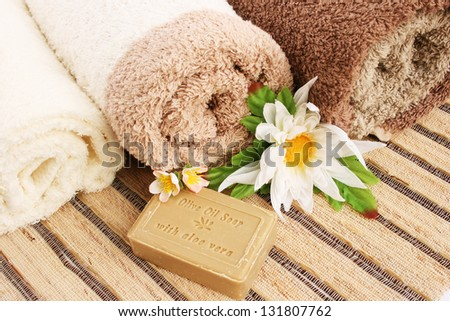 Towels and olive oil soap with aloe vera, flowers on mat background..