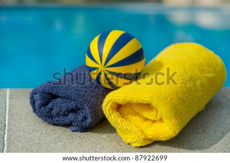 Towels and toys in blue and yellow near the swimming pool - stock photo