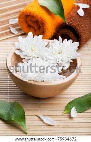 Towels and white daisies in wooden bowl. Spa and body care