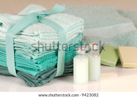 Towels in shades of green with shampoo and soap - stock photo