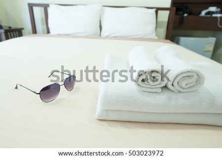 Towels placed on the bed. Sunglasses are placed side by side on site.