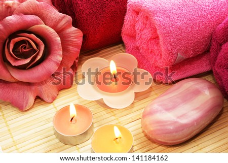 Towels, soap, flower and candles on mat background. - stock photo