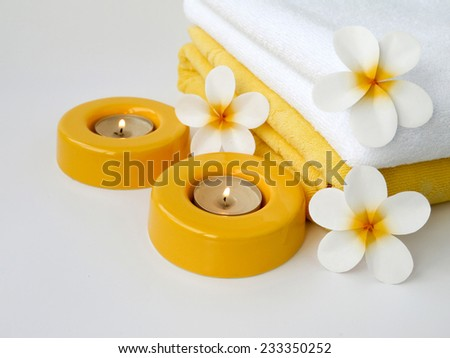 Towels, two candles and three frangipani flowers - stock photo