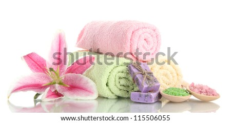 towels with beautiful pink lily, aroma oil and sea salt isolated on white