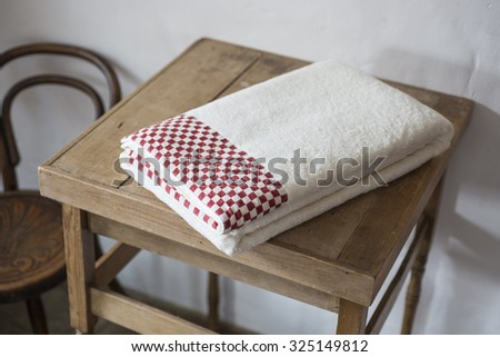 Towels with maroon checkerboard pattern neatly folded and placed on top of small wooden table with wooden chair in the background.