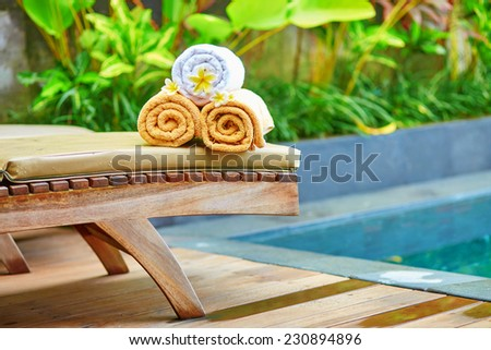 Towels with white frangipani flowers near the pool in a Balinese traditional spa  - stock photo
