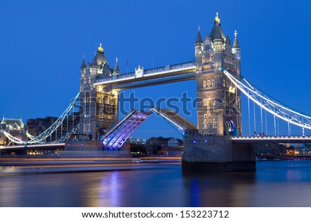 Tower Bridge opens to let a ship pass underneath.   - stock photo