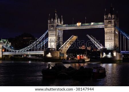 Tower Bridge with a boat passing beneath its raised arches