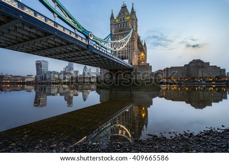 Tower Bridge with blue sky and beautiful water reflection during low tide in London, England - stock photo