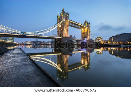 Tower Bridge with blue sky and with beautiful water reflection during low tide in London, England - stock photo