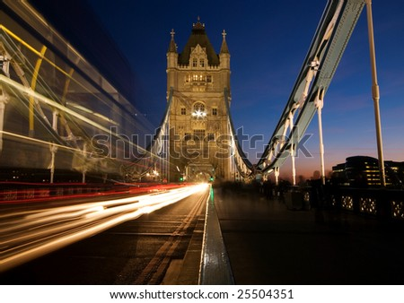 Tower Bridge with motion blur of passing red bus - stock photo
