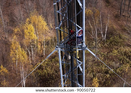 Tower climber inside the guyed tower - seen in the autumn scenery. - stock photo