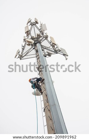Tower climber on monopole tower. - stock photo