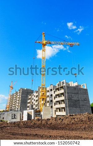 Tower crane on the construction site beneath blue cloudy sky - stock photo