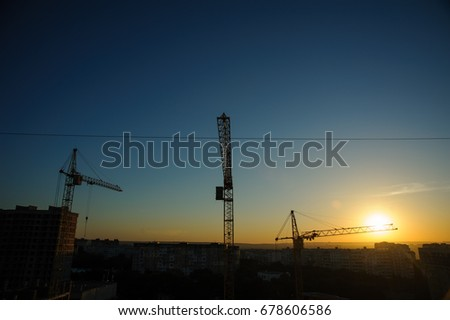 tower cranes silhouette at construction site in sunrise
