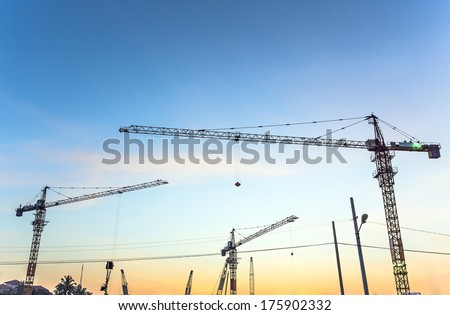 Tower cranes sillouetted against a sunset sky, Sunset cranes - stock photo