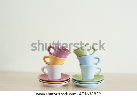 Tower from arranged multicolor coffee cups on wooden table.