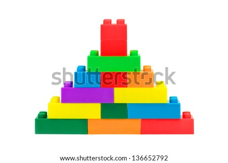 Tower made from plastic colorful toy blocks on white background