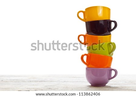 Tower of color cups on old wood table - stock photo