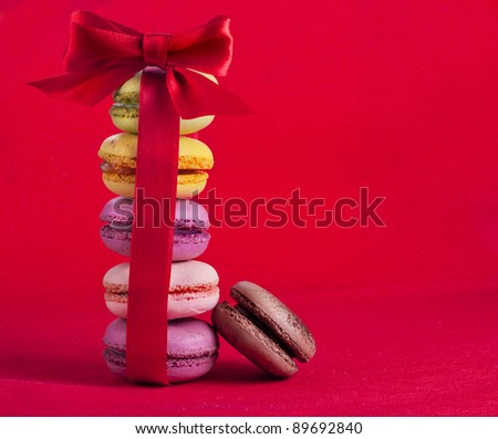 Tower of Colorful  french macaroons with red ribbon bow  on a red  background - stock photo