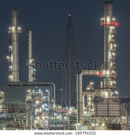 Tower of oil refinery at twilight - stock photo