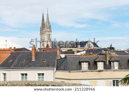 tower of Saint Maurice Cathedral and roofs of houses in Angers city, France - stock photo