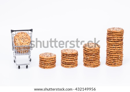 Tower of tasty cookies with sesame and flax seeds and shopping trolley with tasty cookies, isolated with white background  - stock photo