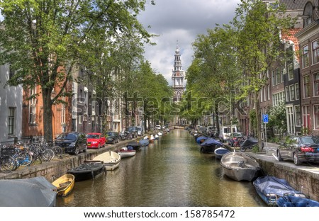 Tower of the Old Church at the end of a canal with little boats in Amsterdam, Holland - stock photo