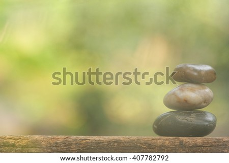 Tower stone on wooden table in the garden with soft look. Concept of tranquility,peace and relaxing. - stock photo