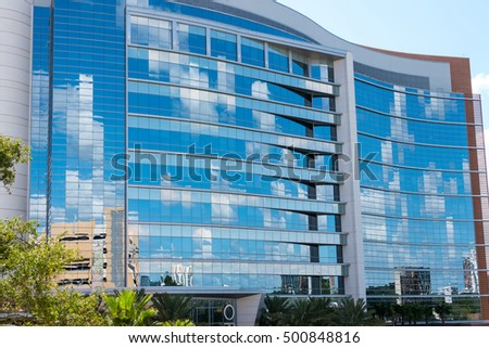 Towering Glass building reflecting clouds and blue sky