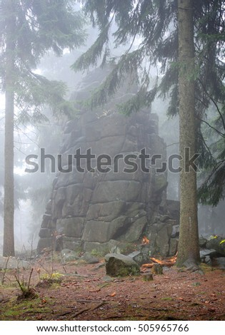 Towering rock in fog in forest