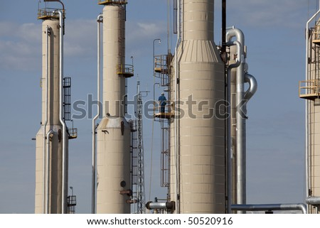 Towers at a gas compressor plant with workmen standing on the platforms. Horizontal shot. - stock photo
