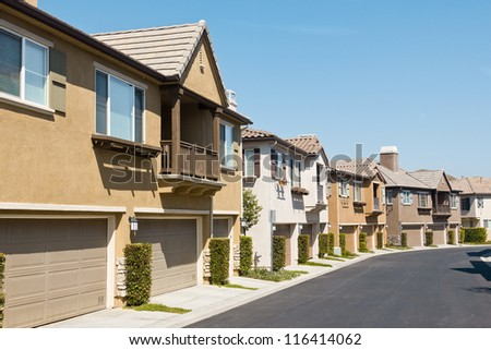 Town homes line up along the road in a new residential neighborhood. - stock photo