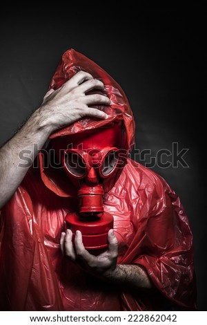 Toxic, A man in a gas mask over  the smoke. black background and red colors - stock photo