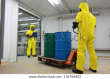 toxic substance delivering - Two specialists in protective uniforms,masks,gloves and boots, dealing with barrels of toxic substance on forklift in factory - stock photo