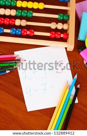 Toy abacus, note paper, pencils on bright background - stock photo
